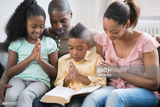 praying together as a family - the god father stock photos and pictures
