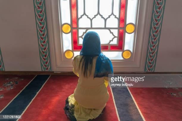betende junge muslimische frau. nahöstliches mädchen betet und liest den heiligen koran. muslimische frau studiert den koran in der moschee - allah stock-fotos und bilder
