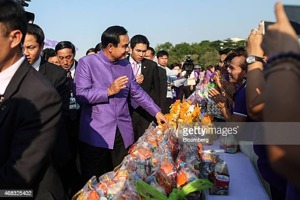 Prayuth Chan-Ocha, Thailand's prime minister and head of the National Council for Peace and Order , center left, speaks with attendees during a...