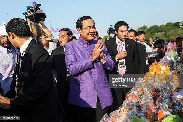 """Prayuth Chan-Ocha, Thailand's prime minister and head of the National Council for Peace and Order , center, performs the traditional Thai """"wai""""..."""
