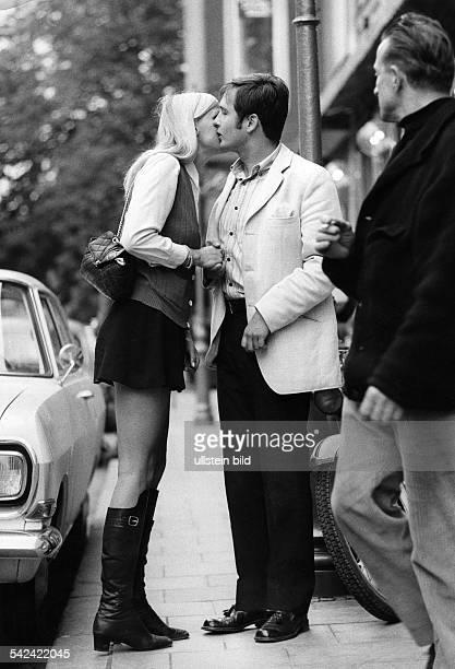 Pärchen bei der Begrüßung bzw Abschied sie trägt Minirock und Stiefel1969