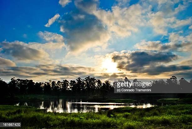 Pôr-do-sol com árvores e lago