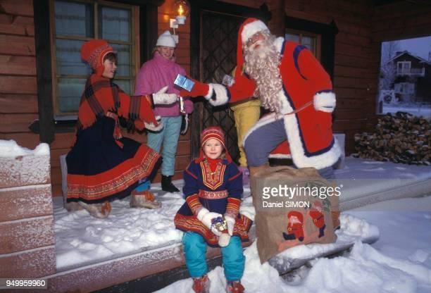 Père Noël avec des enfants en costume traditionnel Lapon en novembre 1988 à Rovaniemi en Finlande