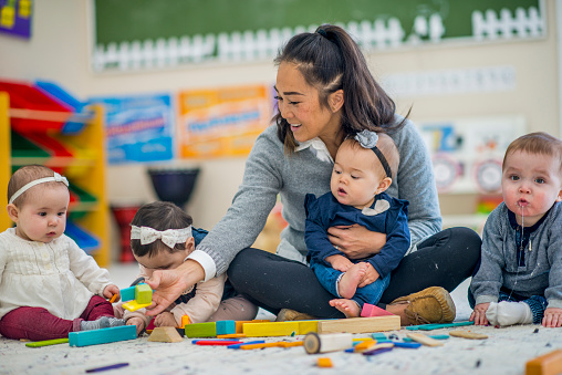 Pre school teacher playing with babies 1063878098