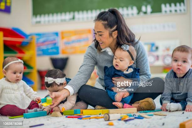 pre school teacher playing with babies - child care stock pictures, royalty-free photos & images