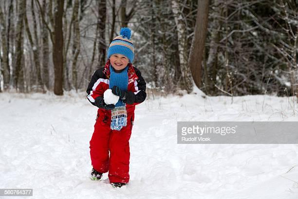 Pre teen boy having fun with snow ball in winter