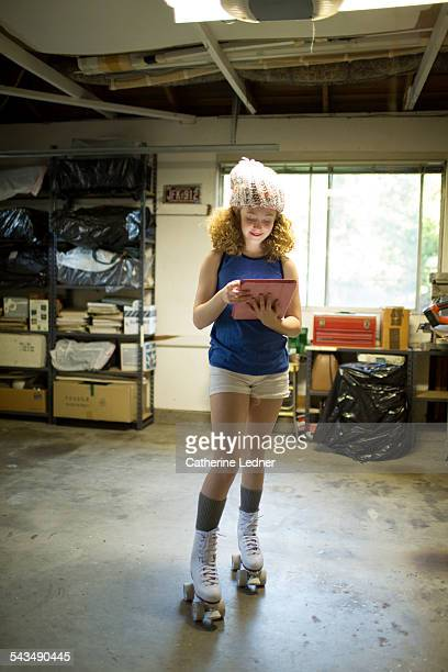 Pre Teen Girl in Garage on Roller Skates and ipad