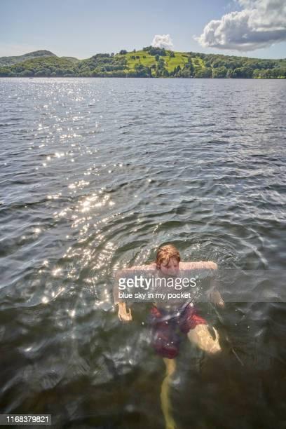 a pre teenage boy wild swimming in a lake on a glorious summers afternoon - pre season bildbanksfoton och bilder