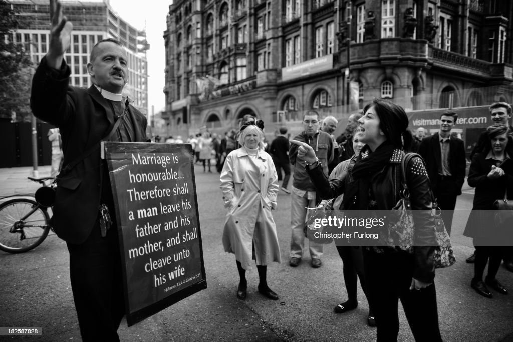 A preacher and a meber of the public argue their religous points outside Manchester Central where the Conservative Party are holding their annual conference on October 1, 2013 in Manchester, England. David Cameron has unveiled a Government pilot scheme for GP surgeries to open from 8am until 8pm seven days, backed by 50 million GBP of funding.