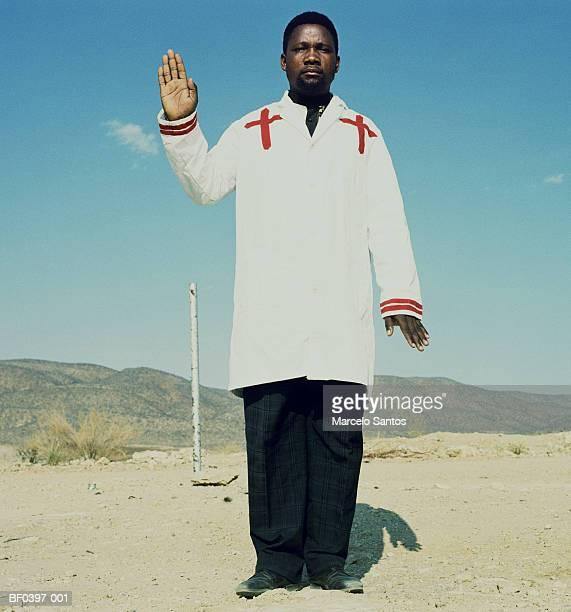 Preacher holding hand up, portrait