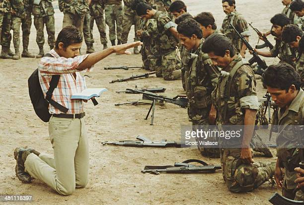 Preacher leads the prayers of group of contra guerillas, 1989. Operating in Nicaragua and Honduras, the group is fighting in opposition to the...