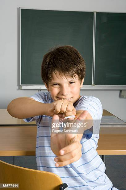 A pre-adolescent boy aiming a rubber band slingshot