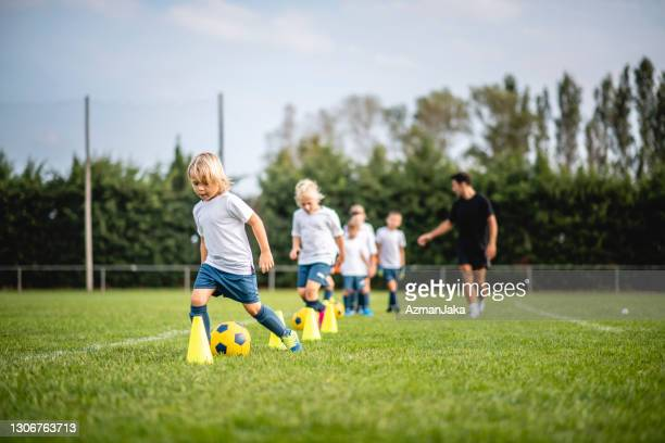 pre-adolescent footballers dribbling around pylons - coach stock pictures, royalty-free photos & images