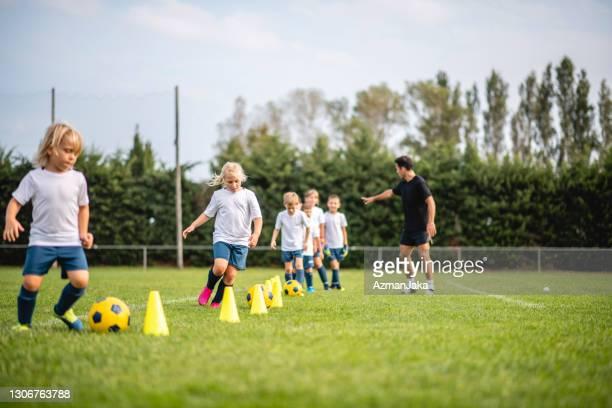 vorjugendliche fußballer dribbeln um pylonen - trainingsdrill stock-fotos und bilder