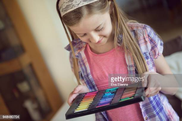 Pre-adolescent girl carrying pallette of multicoloured hair chalks