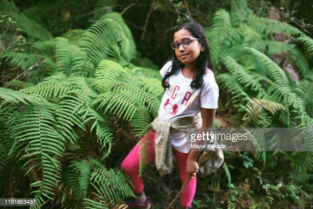 preadolescent girl standing amidst ferns - reality fernsehen stock pictures, royalty-free photos & images