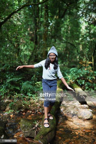 preadolescent girl walking on the fallen tree trunk - pre adolescent child stock pictures, royalty-free photos & images