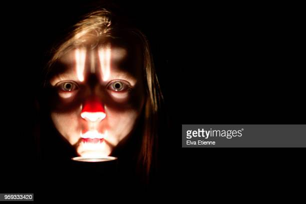 pre-adolescent girl's face, lit by flashlight under her chin - flashlight stock pictures, royalty-free photos & images