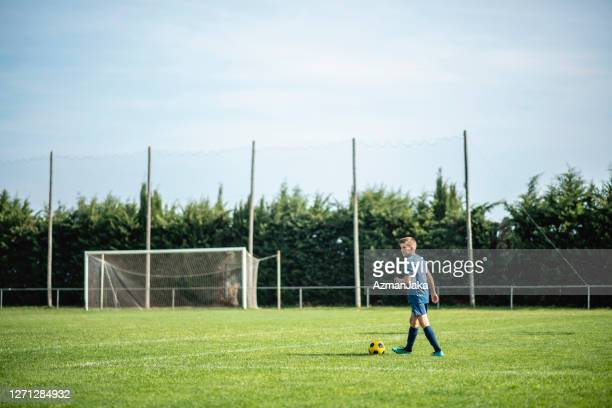 pre-adolescent male footballer dribbling on sports field - football pitch stock pictures, royalty-free photos & images