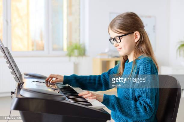 pre-adolescent student playing piano in classroom - keyboard player stock photos and pictures
