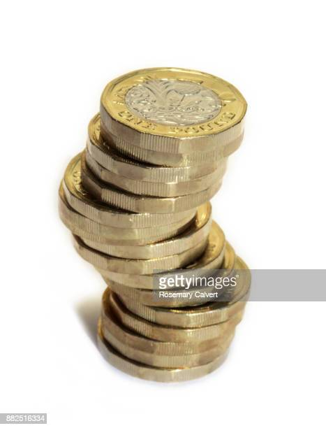 precariously stacked one pound coins on white. - coin photos stock pictures, royalty-free photos & images
