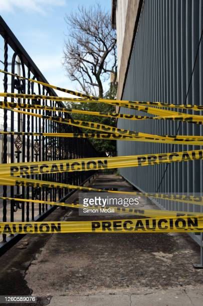 'precaucion' (caution) plastic cordon tape between fence railings on a balcony - cordon tape stock pictures, royalty-free photos & images