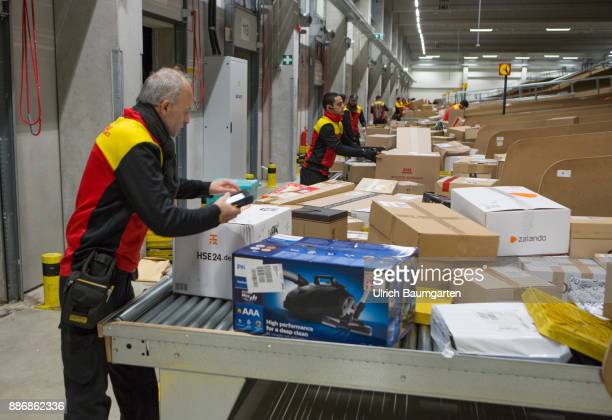 PreChristmas operation in the mechanical extradition base of the German Post DHL Group in Cologne DHL employees scan and sort packages for extradition