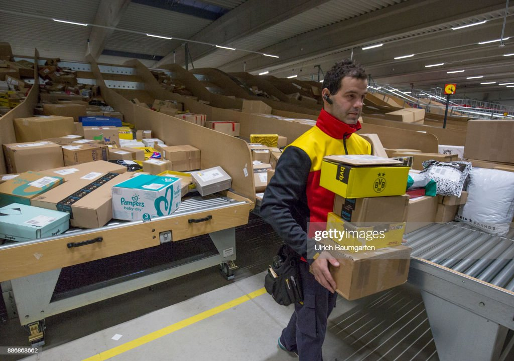 Pre-Christmas operation in the mechanical extradition base of the German Post DHL Group in Cologne. DHL employees sort packages for extradition. : News Photo