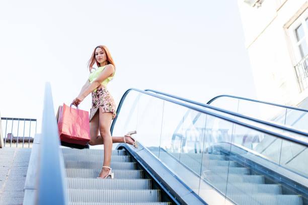 Preciosa mujer bajando de perfil y con un pie en alto por unas escaleras mecanicas de una ciudad.