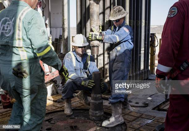 Precision Drilling oil rig operators install a bit guide on the floor of a Royal Dutch Shell Plc oil rig near Mentone Texas US on Thursday March 2...