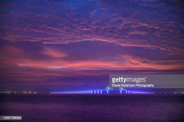 pre-dawn clouds over the illuminated sunshine skyway bridge, fort de soto park, st. petersburg, florida - st. petersburg florida stock pictures, royalty-free photos & images