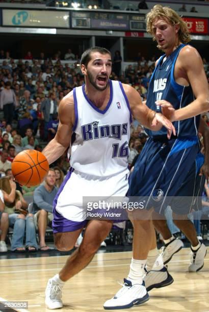 Predrag Stojakovic of the Sacramento Kings drives the ball against Dirk Nowitzki of the Dallas Mavericks October 22 2003 at Arco Arena in Sacramento...