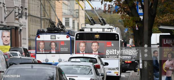 Preelection placards of the proKremlin social democratic party Harmony are on display on buses in Riga Latvia on October 3 on the left is a placard...