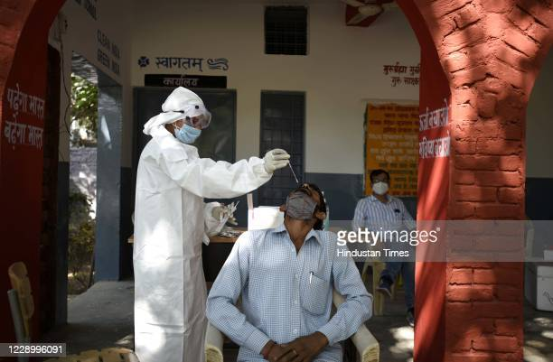Preeti, a health worker, collects a swab sample for Reverse Transcription-Polymerase Chain reaction based coronavirus testing at Government Middle...