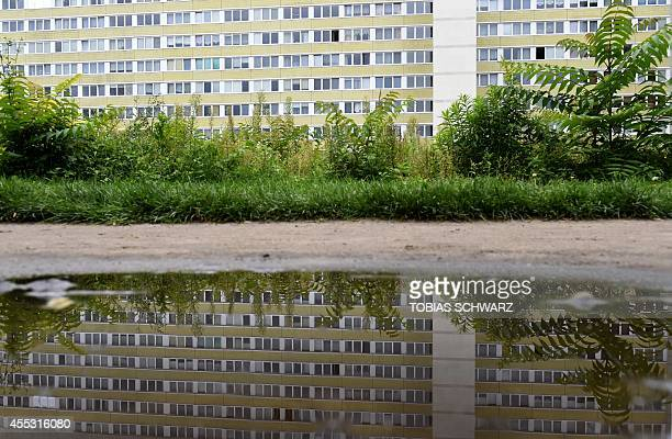 """Prefabricated block of flats, built during East-German days and known as """"Plattenbau"""", is reflected in a puddle of rain water in the eastern German..."""