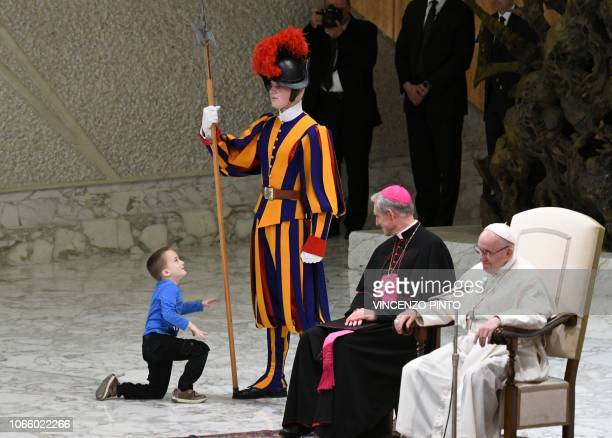 TOPSHOT Prefect of the Papal Household Georg Ganswein watches a boy who came from the audience onto the stage play with a Swiss Guard's spear as Pope...
