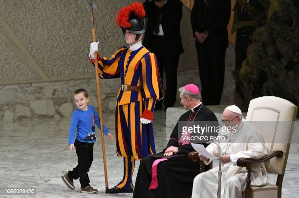Prefect of the Papal Household Georg Ganswein watches a boy who jumped from the audience onto the stage interact with a Swiss Guard as Pope Francis...