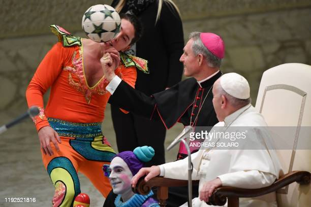 Prefect of the Papal Household German Archbishop Georg Gaenswein spins a ball on his finger as Pope Francis looks on as artists form a Cuban circus...