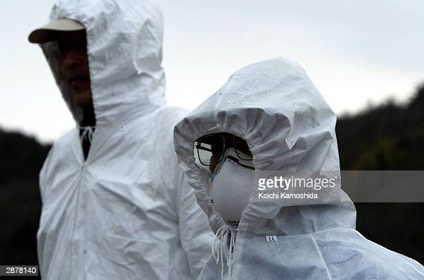 Prefectural workers investigating the bird flu epidemic in the town of Ato look on January 18, 2004 in the Yamaguchi Prefecture, Japan....