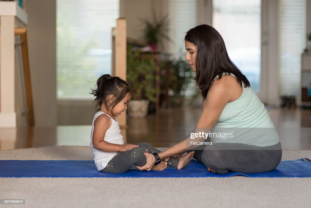 Pregant ethnic mother doing yoga with her young toddler girl : Stock Photo