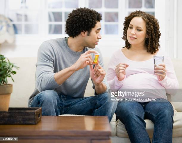Pregnant African couple looking at medication