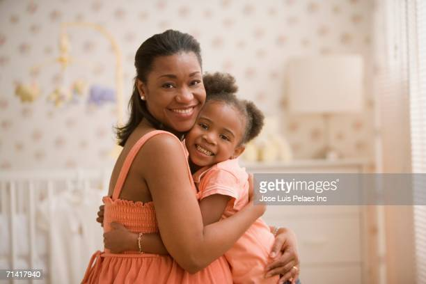 Pregnant African mother hugging young daughter