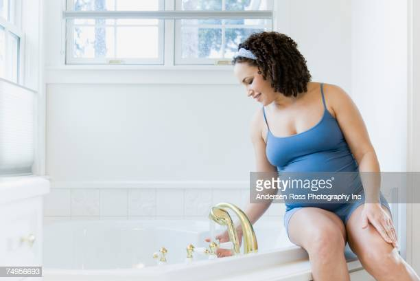 Pregnant African woman running bath