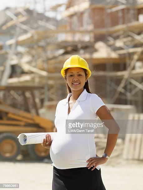 Pregnant Asian businesswoman at construction site