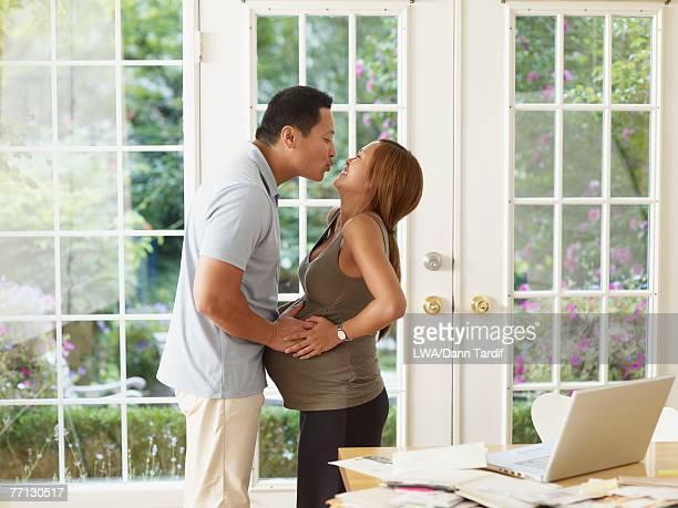Pregnant Asian couple kissing