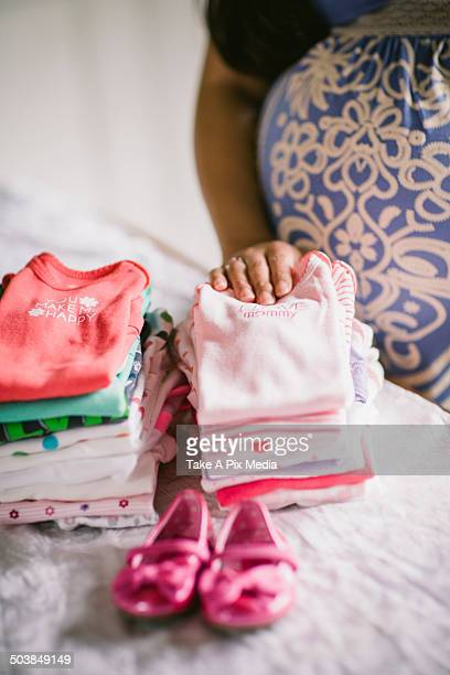 Pregnant Asian woman folding baby clothes