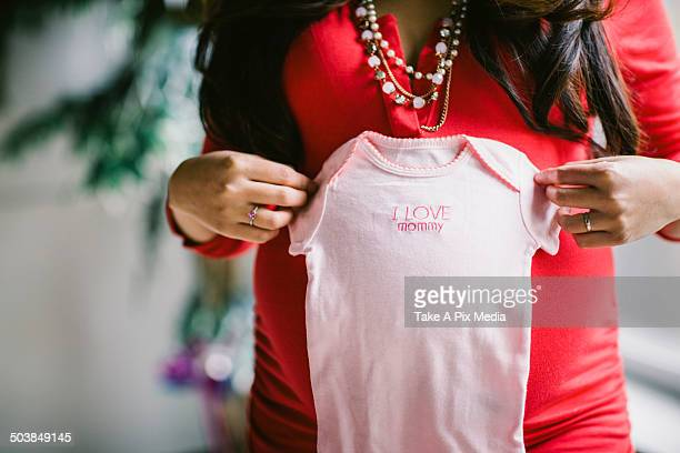 Pregnant Asian woman holding baby clothes