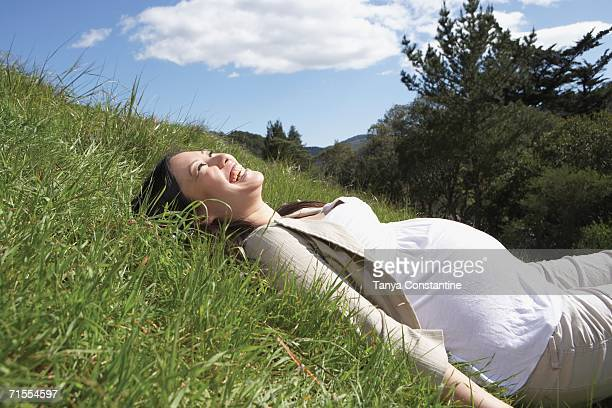 Pregnant Asian woman laying in the grass