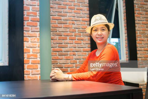 Pregnant Asian Woman with Straw Boater Hat and red Sweater