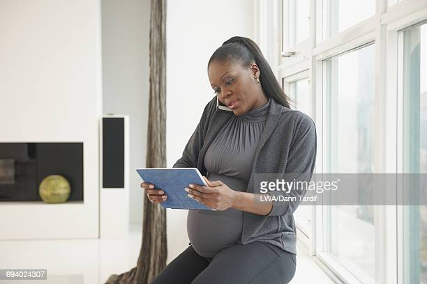 Pregnant Black businesswoman using digital tablet and cell phone